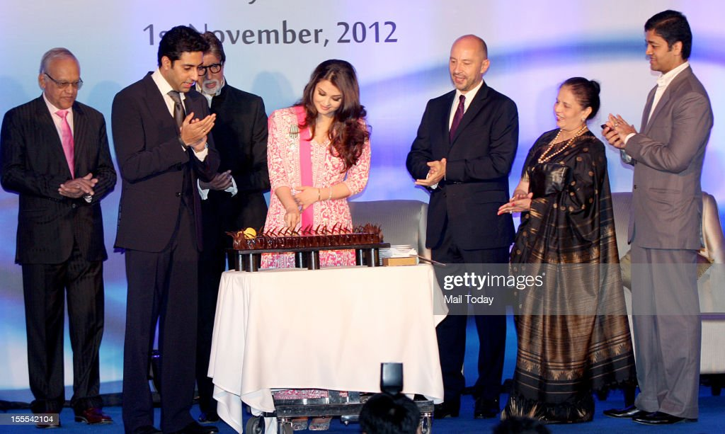 Bollywood actress Aishwarya Rai Bachchan cuts a cake on her birthday as her husband Abhishek Bachchan, father-in-law Amitabh Bachchan and French Ambassador to India, Francois Richier (3rd R) applaud at a function in Mumbai on Thursday. Aishwarya was conferred with the French civilian award, Officer Dan Ordre Arts et des Lettres at the function.