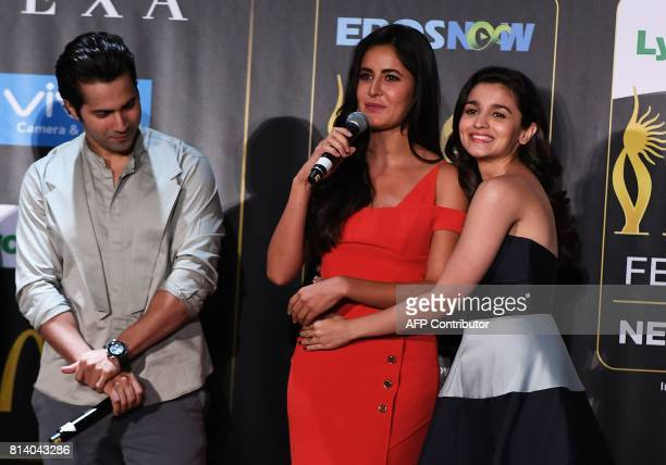 Bollywood actress Alia Bhatt hugs Katrina Kaif as she speaks while actor Varun Dhawan looks on during a press conference ahead of the 18th...