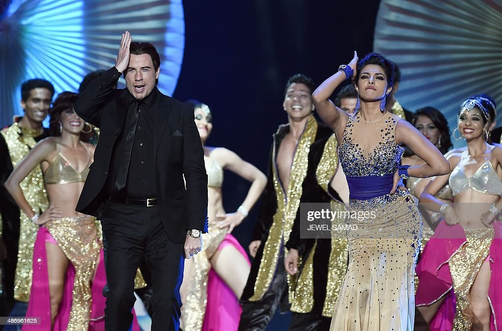 Bollywood actress Priyanka Chopra (R) dances and Hollywood actor John Travolta dance on stage during the fourth and final day of the 15th International Indian Film Academy (IIFA) Awards at the Raymond James Stadium in Tampa, Florida, April 26, 2014.AFP PHOTO/Jewel Samad