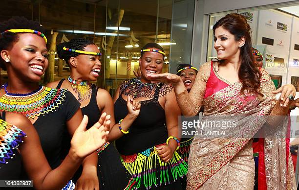 Bollywood actress Raveena Tandon dances with traditional Zulu dancers during the launch of the South Africa India Film and Television Awards in...
