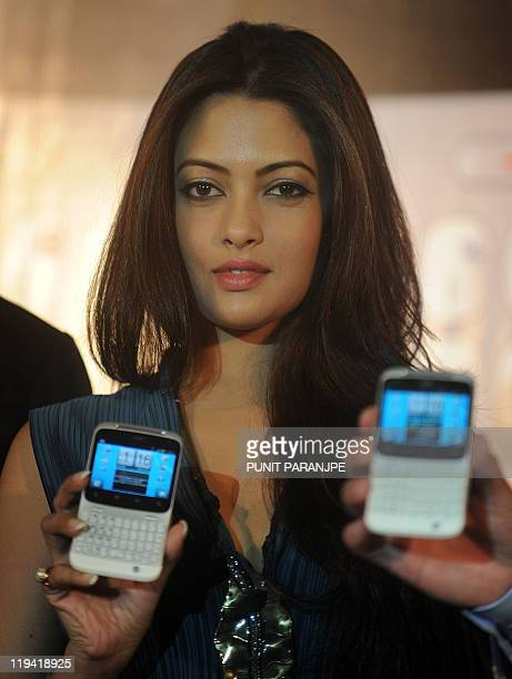 Bollywood actress Riya Sen holds the new HTC 'ChaCha' mobile handset during a product launch event in Mumbai on July 20 2011 The device is expected...