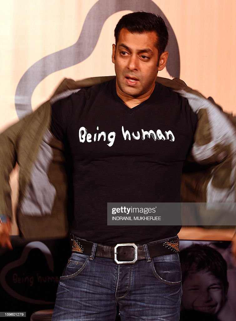 Bollywood film actor Salman Khan takes off his jacket during the launch of his 'Being Human' flagship clothing store in Mumbai on January 17, 2013. Khan announced the pan-India launch of his flagship retail store for 'Being Human' fashion apparel after having already launched in Paris, Belgium, Spain and Dubai. AFP PHOTO/ INDRANIL MUKHERJEE