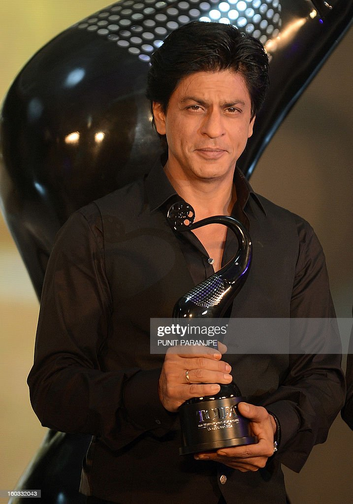 Bollywood film actor Shah Rukh Khan gestures as he holds a trophy during a function to announce new Times Of India Film Awards (TOIFA) Bollywood awards in Mumbai on January 29, 2013. TOIFA Bollywood awards will take place in Vancouver, Canada from April 4 to 6, 2013.