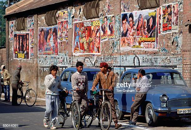 'Bollywood' film posters advertising the latest movies in Agra India Young men chatting together while pushing their bicycles