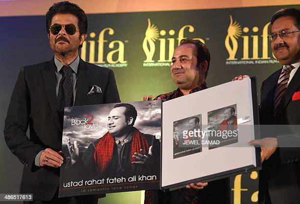 Bollywood singer Rahat Fateh Ali Khan flanked by Bollywood actor Anil Kapoor and an unidentified official presents his latest release during a press...