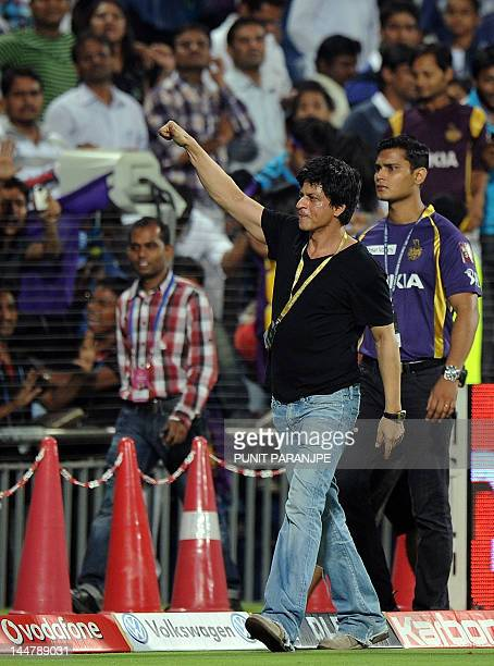 Bollywood star and part owner of Kolkata Knight Riders team Shah Rukh Khan gestures towards fans as he walks in the ground after his team won the IPL...