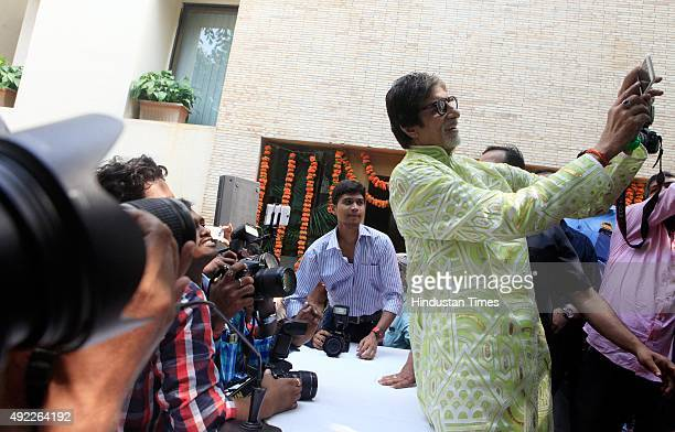 Bollywood superstar Amitabh Bachchan takes selfie with media and fans on his birthday at his residence Janak Bungalow on October 11 2015 in Mumbai...