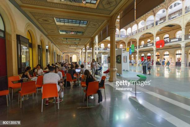 Tourists and residents rest in the shade on 'Sala Borsa' with airconditioned for protection from the sun and heat on June 23 2017 in Bologna Italy An...