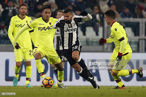 Bologna's defender Erick Pulgar from Chile fights for the ball with Juventus' midfielder Tomas Rincon from Venezuela during the Italian Serie A...