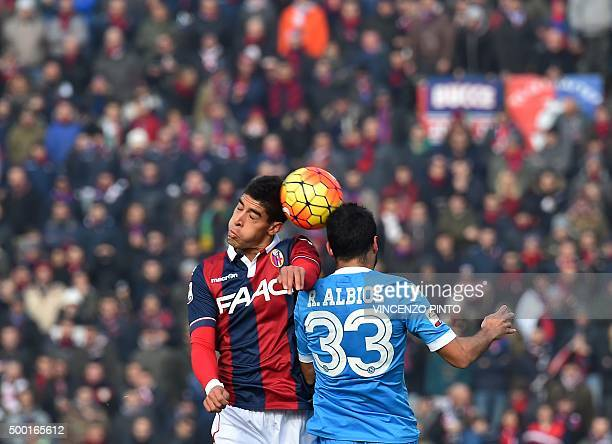 Bologna's defender from Morocco Adam Masina jumps for the ball with Napoli's defender from Spain Raul Albiol during the Italian Serie A football...