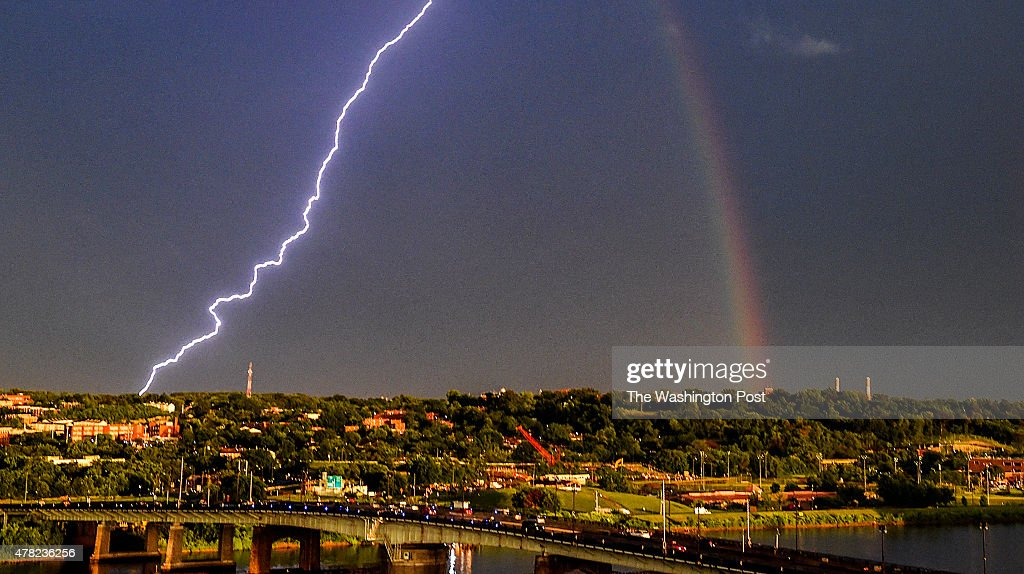 A bolt of lightning strikes across the Anacostia river as a rainbow graces the sky near Nationals Park as the Washington Nationals and Atlanta Braves were in a two plus hour rain delay on June 23, 2015 in Washington, DC.