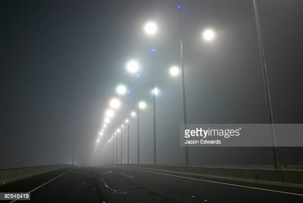 Winter fog engulfs freeway lighting on cross-town city bridge.