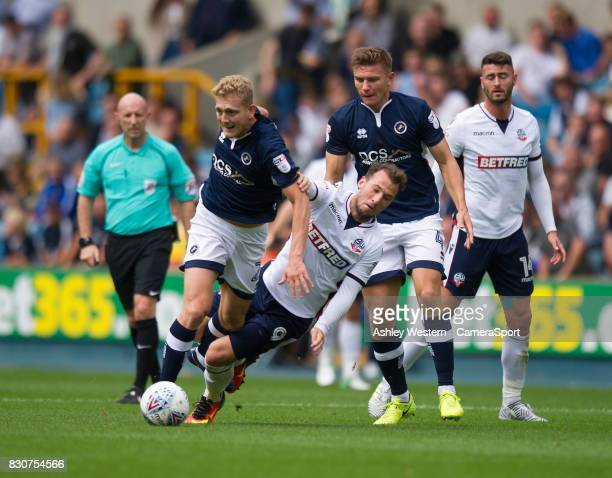 Bolton Wanderers' Adam Le Fondre is tackled by Millwall's George Saville during the Sky Bet Championship match between Millwall and Bolton Wanderers...