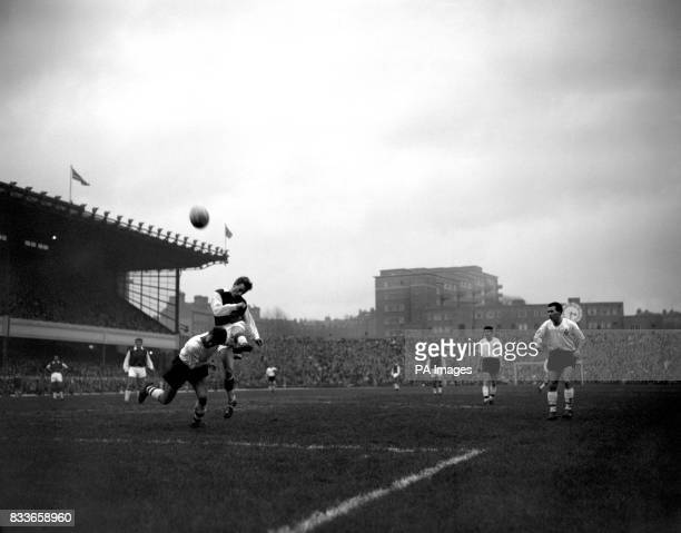 Bolton Wanderers' Graham Stanley challenges Arsenal's George Eastham as the latter lashes the ball into the crowd