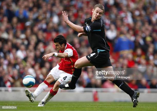 Bolton Wanderers' Kevin Nolan challenges Arsenal's Francesc Fabregas for the ball