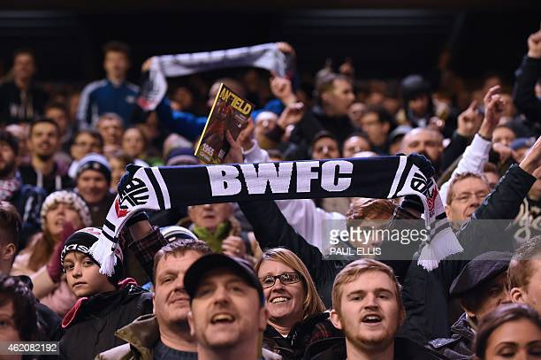 Bolton Wanderers' supporters wave their scarves in the air after the FA Cup fourth round football match between Liverpool and Bolton Wanderers at...