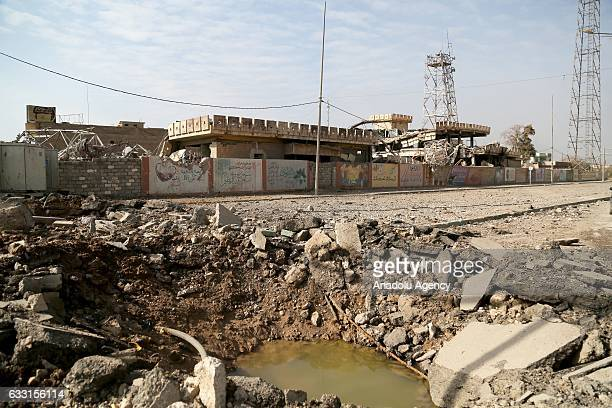 A bomb crater and debris of building are seen after the city has been retaken from Daesh terrorists in Mosul Iraq on January 30 2017