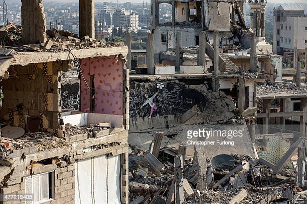 Bomb damaged homes still scar the landscape with some families still living in the dangerously unstable buildings that scar Gaza on June 15 Gaza City...