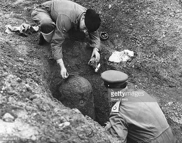 Bomb disposal experts pour Walpamur Petrifying Liquid over an unexploded bomb in the East End of London 1960s