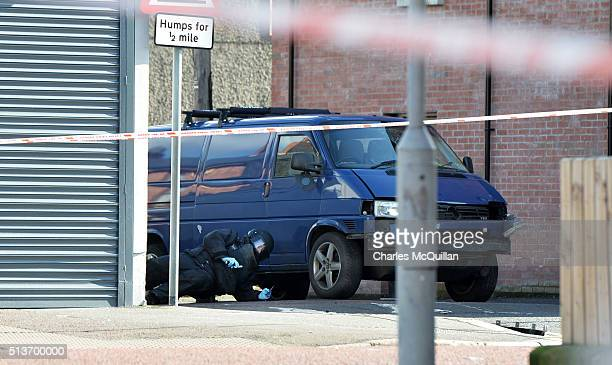 A bomb disposal unit officer inspects the damaged van following a suspected car bomb attack on a prison officer at Hillsborough Drive on March 4 2016...