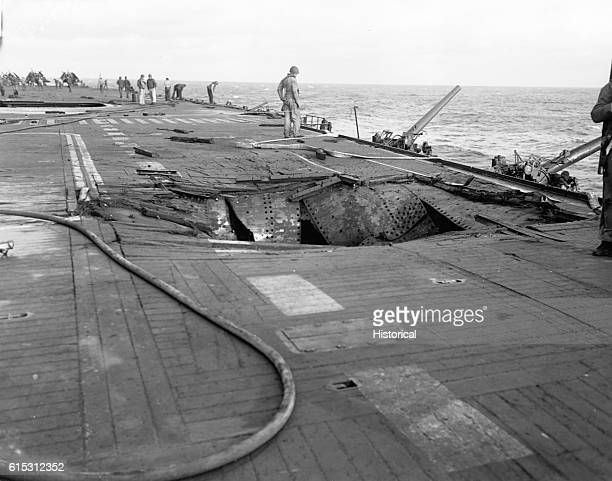 A bomb hole in the flight deck of the USS Saratoga port side results of Japanese dive bomber attacks off Iwo Jima ca 1945   Location near Iwo Jima...