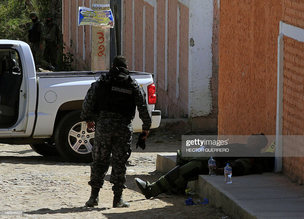 A bomb squad member (R) takes a rest after defusing a grenade found at a crime scene in Hostotipaquillo, Jalisco State, Mexico on January 29, 2013. An unidentified armed command killed three people, including the police director of the municipality Hostotipaquillo, Lucio Rosales Astorga. AFP PHOTO/Hector Guerrero
