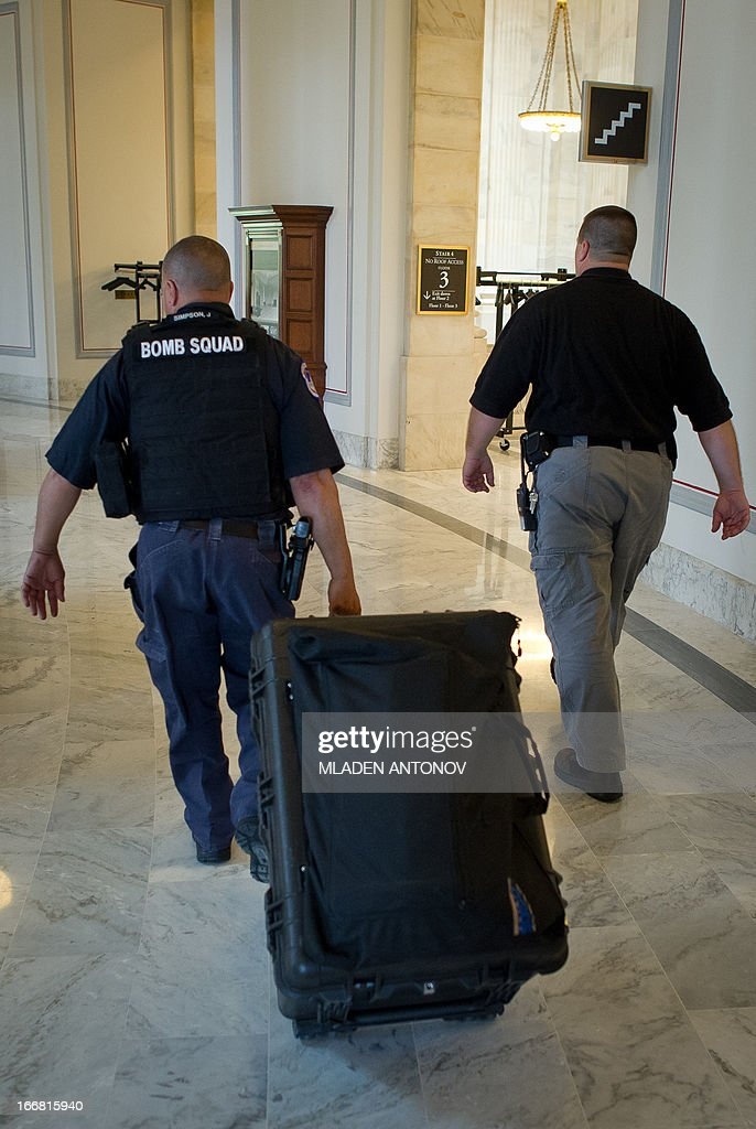 Bomb squad members leave the Russell Senate office building after reports of a suspicious package closed temporary parts of the building in Washington DC, April 17, 2013. At the US Capitol, sections of two Senate office buildings were briefly cordoned off amid reports of a suspicious package. Capitol Police later said results of tests conducted at the Hart Senate office building were negative and the closed-off areas were reopened. US Capitol Police confirmed one man was being questioned. 'Right now they are interviewing a person but that person is not in custody. He has not been detained,' a US Capitol Police officer said. AFP PHOTO / Mladen ANTONOV