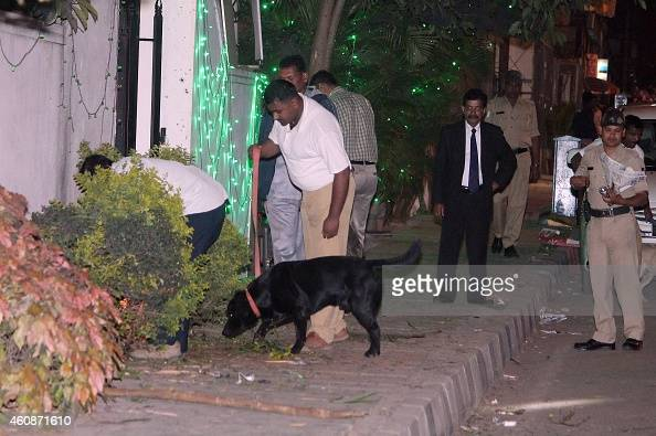 Bomb squad personnel along with sniffer dogs scour the blast site for evidence following a low intensity blast from an Improvised Explosive Device...