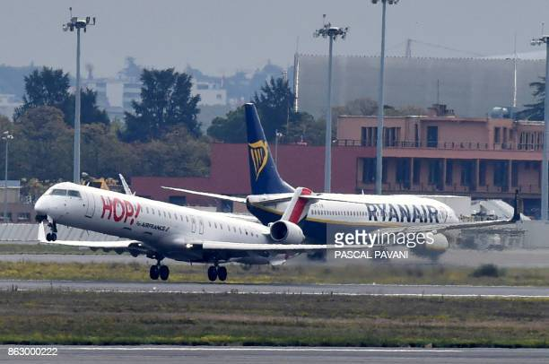 A Bombardier CRJ 1000 of French lowcost Hop airline company takes off next to an aircraft of Irish lowcost Ryanair airline company on October 19 2017...