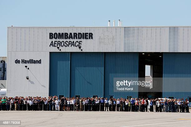 Bombardier employees watch the flyby of the new CS100 commercial jet near their plant in Toronto Ontario