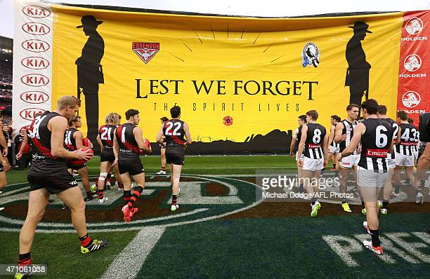 Bombers and Magpies walk to the Anzac banner during the round four AFL match between the Essendon Bombers and the Collingwood Magpies at Melbourne...