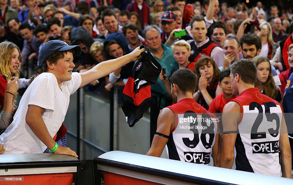 A Bombers fan holds up a Bombers jumper to Jeremy Howe and Tom MacDonald of the Demons who walk to the rooms after a big loss during the round two AFL match between the Essendon Bombers and the Melbourne Demons at Melbourne Cricket Ground on April 6, 2013 in Melbourne, Australia.