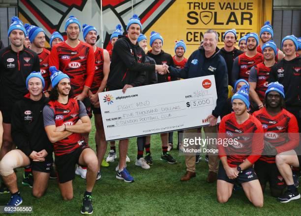 Bombers legend Neale Daniher poses with nephew Joe Daniher of the Bombers and his teammates during a cheque presentation to fight MND at the Essendon...