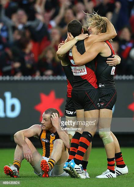 Bombers players celebrate winning whilst Jarryd Roughead of the Hawks looks dejected the round two AFL match between the Essendon Bombers and the...
