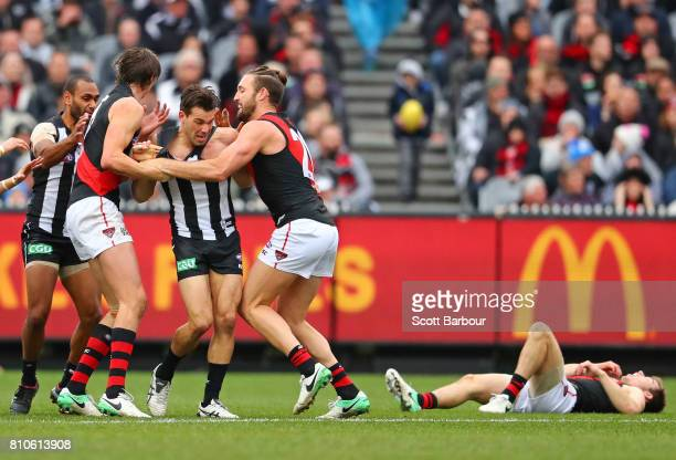 Bombers players wrestle with Levi Greenwood of the Magpies after a high hit on Zach Merrett of the Bombers during the round 16 AFL match between the...