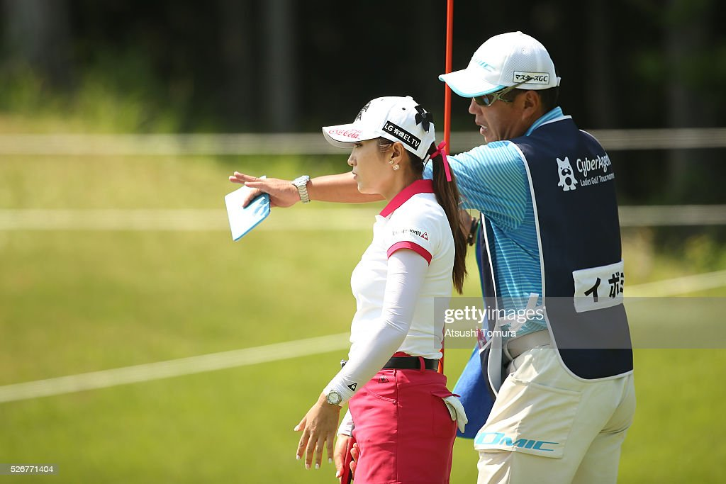 Bo-Mee Lee of South Korea lines up her second shot with her caddie on the 14th hole during the final round of the CyberAgent Ladies Golf Tournament at the Grand Fields Country Club on May 1, 2016 in Mishima, Japan.