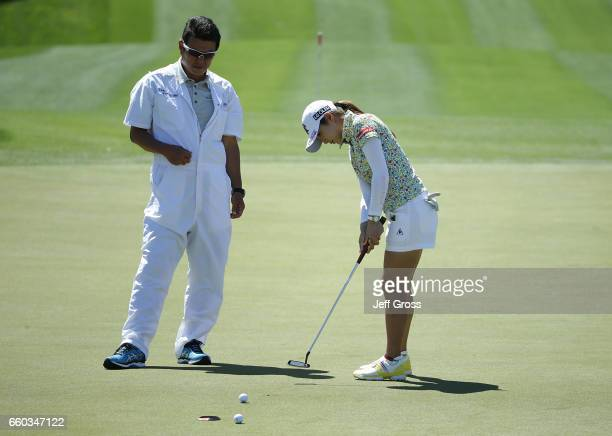BoMee Lee of the Republic of Korea putts on the fourth green as her caddie Nori Shimizu looks on during a pro am at Mission Hills Country Club on...