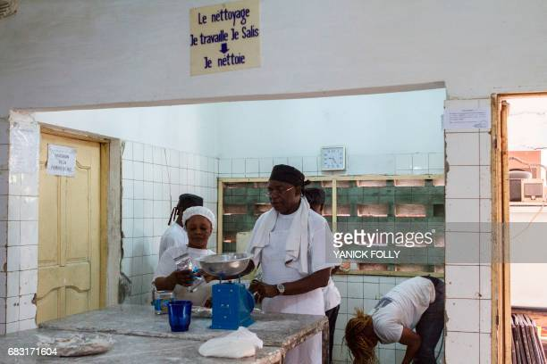 Bonaventure Boma prepares bread in his bakery in Lome on April 3 2017 Dressed in an apron Bonaventure Boma reprimands his employees out of the oven...