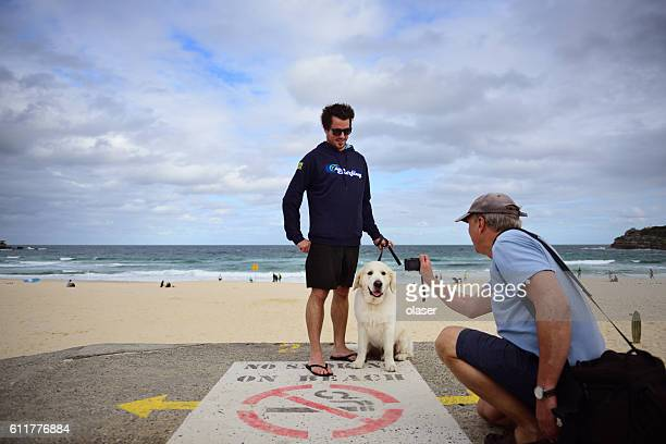 Bondi beach, man taking picture of young adult with dog