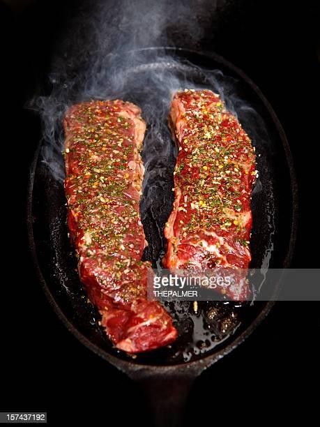 Boneless Short Ribs steak frying in a pan