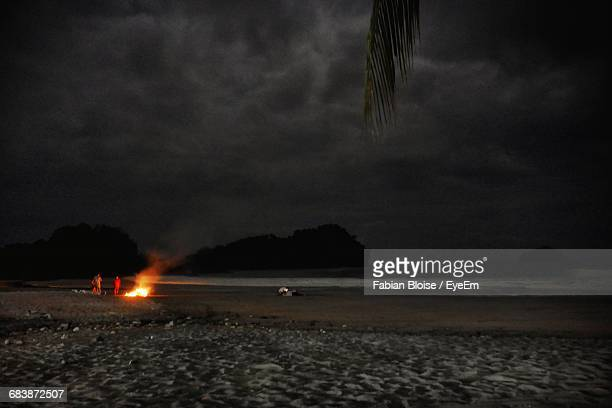 Bonfire At Beach Against Cloudy Sky During Night
