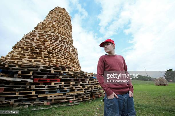 Bonfire builder Ryan Preston poses beside the Doonbeg bonfire in Rathcoole in north Belfast Northern Ireland on July 10 ahead of the traditional 11th...