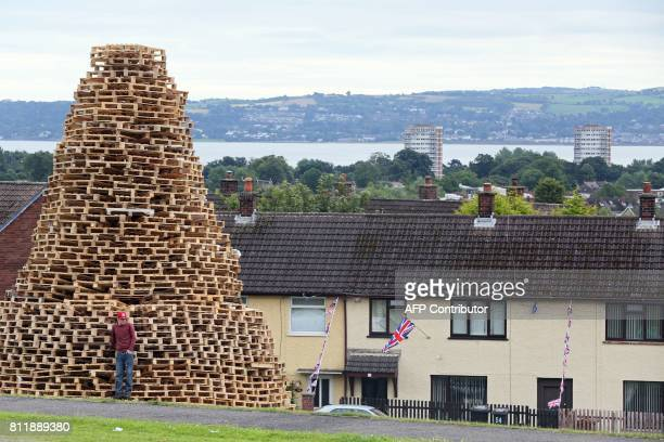 Bonfire builder Ryan Preston poses for a photograph on the Doonbeg bonfire in Rathcoole in north Belfast Northern Ireland on July 10 ahead of the...