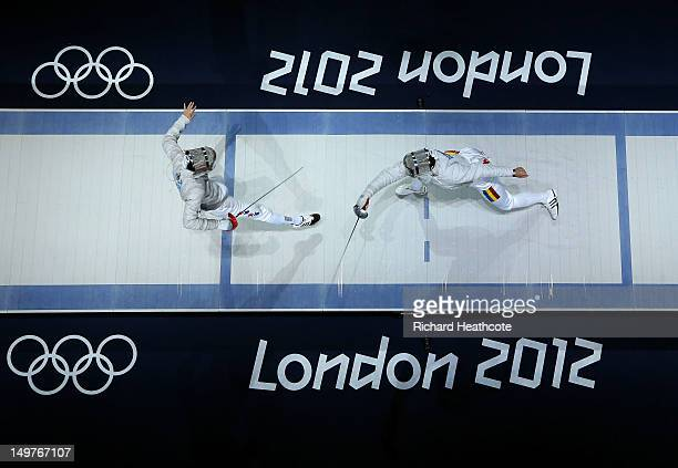 Bongil Gu of South Korea competes against Rares Dumitrescu of Romania during the Men's Sabre Team Fencing on Day 7 of the London 2012 Olympic Games...