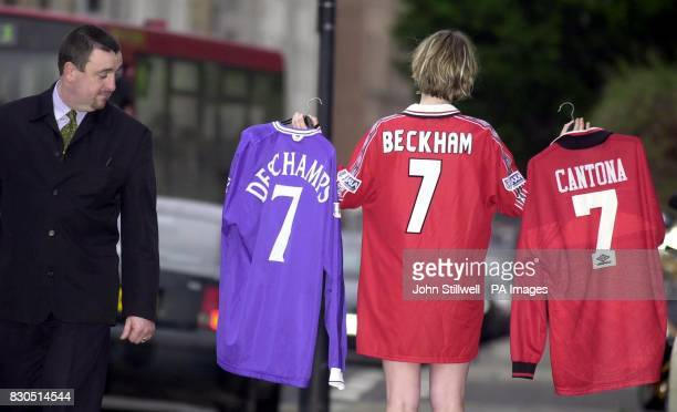 Bonhams and Brooks employee Laura Brownlow wearing a David Beckham 1999 cup final shirt carries the shirt of his former team mate Eric Cantona and...