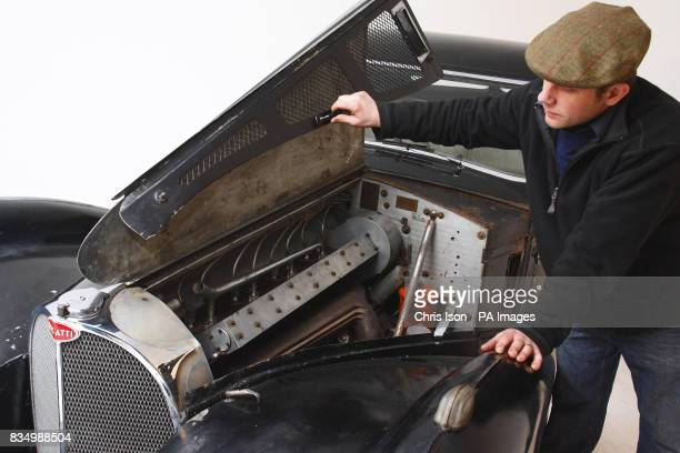 Bonhams auctioneer's consultant Nicholas Benwell looks under the bonnet of a rare 1937 Bugatti Type 57S in Hartley Witney Hampshire which will go to...