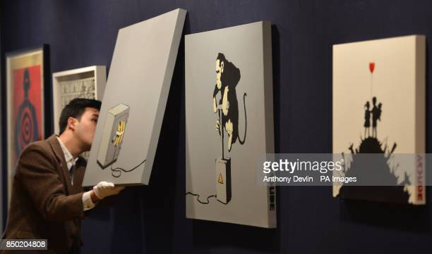 Bonham's cataloguer Victor Seaward hangs Banksy's Monkey Detonator 2002 during the preview for Climbing The Walls With Banksy at Bonham's Urban Art...