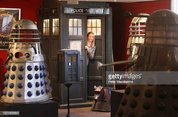 Bonhams employee Katherine Boyle looks out from a full size prop of a Dr Who Tardis as Daleks and a K9 robot look on on June 21 2010 in London...