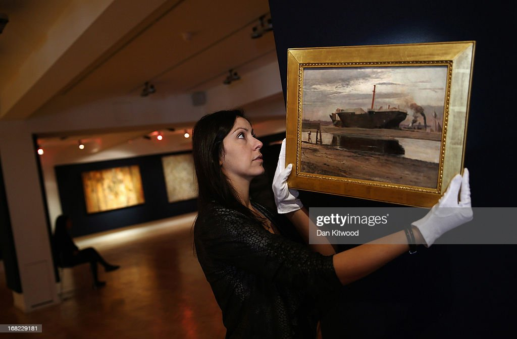 A Bonhams employee moves a piece of work by Australian artist Tom Roberts entitled 'The old Sacramento', 1885, at Bonhams auction house on May 7, 2013 in London, England. The piece is expected to fetch between $100,000 - 150,000 AUS (approximately £65,000- £100,000 GBP) when it goes up for auction at an Australian Art sale at Bonhams in Sydney on June 26, 2013. The collection, which has never been seen before in public belongs to Neighbours producer Reg Grundy.