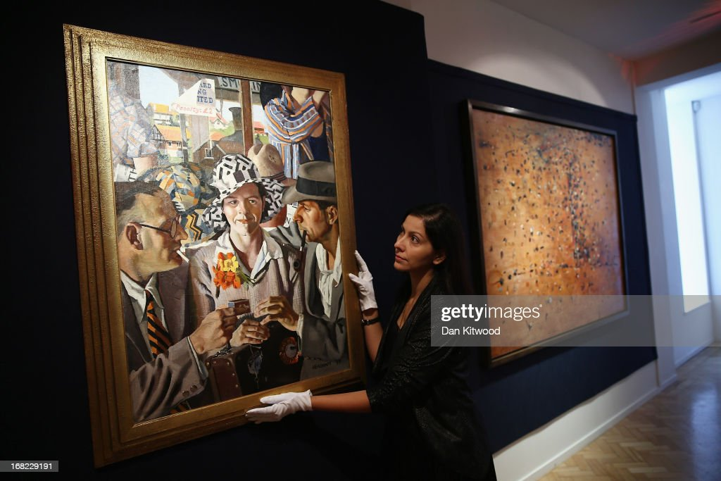 A Bonhams employee poses beside a piece of work by Australian artist Herbert Badham entitled 'Travellers', 1933 at Bonhams auction house on May 7, 2013 in London, England. The piece is expected to fetch between $200,000 - 300,000 AUS when it goes up for auction at an Australian Art sale at Bonhams in Sydney on June 26, 2013. The collection, which has never been seen before in public belongs to Neighbours producer Reg Grundy.